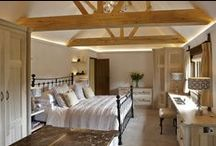 Vaulted Ceiling Bedroom / The aim with this bedroom design was to bring volume & light to a part of the house with low ceilings & small interconnecting rooms. We realised that it would be possible to lift the roof space & design an unusual & beautiful vaulted feature with large oak trusses & beams creating a feeling of spaciousness, warmth & grandeur. The bedroom furniture & bathroom furniture is crafted in washed tulip wood which has a silvery blond quality in daylight & further enhances the light & airy feel.