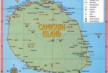 """Camiguin Island / Camiguin Island, the """"The Island Born of Fire"""", is an island province in the Philippines located in the Bohol Sea, about 10 kilometres (6.2 mi) off the northern coast of Mindanao. Camiguin is the second-smallest province in the country both in population and land area after Batanes. The provincial capital is Mambajao, which is also the province's largest municipality both in area and population."""