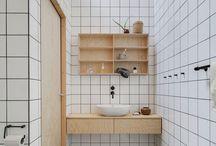 VERBOUWING - BADKAMER / Kleuren: wit, zwart, hout (roze of groen). Muur en vloer: alleen vloer en douchehok betegelen, rest verven. Tegels: alles marmer(look) of grijs beton op vloer en witte/roze/groene vierkantjes/hexagon in douchehok. Donkere voeg of  zonder. Douchecabine: muur, niet tot plafond, met ingebouwde plank Meubels: zwevend met 1 lade van hout (eiken/underlayment). Inbouwkast met houten deuren. Vierkante mat witte wasbak. Kranen: zwart.