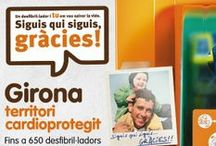"""Girona Territori CardioProtegit   / Dipsalut impulsa el programa """"Girona, territori cardioprotegit"""" que suposa la implantació d'una xarxa de desfibril•ladors automàtics d'accés lliure, situats al carrer i a espais públics com façanes d'equipaments municipals i acompanyant equips d'emergències com ara policia local, protecció civil... L'objectiu és poder intervenir ràpidament en el cas que una persona pateixi una aturada cardíaca. Amb aquesta iniciativa s'aspira a reduir entre un 25 i un 30% la mortalitat per causa de mort sobtada."""