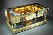 """THE SAILOR Coffee Table / This complex outstanding piece from the Arcade Furniture is made from the original renewed playfield of the Sinbad pinball built by Gottlieb in 1978. The outer decoration featuring original, clear coated pages from """"The Seven Voyages of Sinbad"""" from 1926. The glass cage in the mid section of the table holds one golden ram's head and the skull is illuminated. The cage is bordered with mirrors on top and bottom, creating a magical effect while trapping the light."""