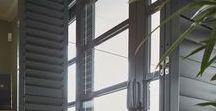 Zonnelux | Zwarte shutters in klassieke villa / In deze klassieke villa creëren de zwarte shutters van Zonnelux een warme sfeer. De donkere shutters zorgen voor een mooi contrast in de witte keuken. De shutters voor de openslaande duren zijn voorzien van een vouwrailsysteem, waardoor de deuren niet gehinderd worden.