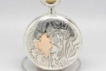 Belo Omega Caixa Cinzelada em Prata, ca.1915 / Bela peça da marca Omega, produzida ca.1915. Trata-se de um relógio que mede 4.9 cm de diâmetro, e possui uma magnífica caixa em prata toda cinzelada com acabamento parcial a ouro. Bordo com figuras geométricas.