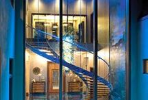 "Spiral Staircase / Joins master bedroom to formal dining - glass, flood lit with deep teal feature wall, ""cloud"" LED light, separated by chain curtain from dining. Exterior copper cladding."