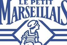 """Candidature L'Oréal - Le Petit Marseillais / La marque Le Petit Marseillais joue sur la tradition méditerranéenne et la nature. La marque veut raconter une histoire : celle de la mère ou de la grand-mère qui transmet ses secrets de beauté à sa fille et petite fille. Le slogan """"Restons Nature"""" insiste sur les ingrédients naturels des produits (huile d'argan, karité, citron etc.). Le packaging est sobre, les couleurs sont souvent chaudes (exception pour les produits cheveux longs (gris) et antipelliculaire (bleu)). Produits gorgés de soleil."""