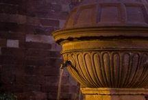 Prades / El poble es troba al centre de les muntanyes de Prades, a 950 m d'altura. La vila, antiga capital del comptat de Prades –vinculat a la casa reial catalana: la reina Margarida de Prades fou muller de Martí I l'Humà–, presenta un important conjunt monumental amb la bella i característica pedra rogenca del Triàsic que li ha donat el sobrenom de la vila vermella. Cal admirar els portals de les muralles, la plaça porticada, la famosa i bella font esfèrica del Renaixement i el basament de les torres.