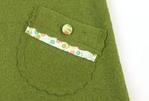 Trägerkleid Josefin / hat zwei schräg aufgesetzte Taschen, die mit Baumwollband und Knöpfen verziert sind