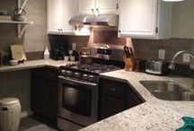 Burbank Condo Kitchen Renovation / Rustic yet elegant kitchen with accents inspired by nature such as wood tile on the walls, natural stone look floor tiles, granite counter tops, duo toned cabinets, wine and white brass accents, contemporary faucet, stainless steel, soft green paint, masculine