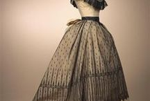 1868, bustle / 1868 saw a fullness appear at the back of the skirt. A bustle is a pad that emphasized the posterior. Used in the late 1700s when swagged up skirts made a large rear end fashionable, they eventually became the prime focus of fashion. By the later 1800s, rear pads were called bustles.