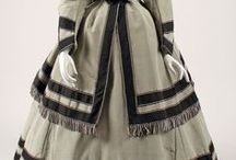 1867 / In the 1860's, skirts reached their fullest, hats became smaller. Decoration became more geometric, and striped fabrics were also popular. By the end of the period, the full skirts became asymmetrical, with fullness pushed to the back, a precursor of the next major fashion shift, bustle.