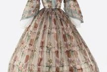 1856, cage crinoline/hoops, smoother surface, pantalettes / cage crinoline/hoops were invented; The skirts became so full that by the late 1850's hoops were needed to support them, as the heavy layers of petticoats could no longer achieve the desired effect. Flounces gradually disappeared in favor of a skirt lying more smoothly over the petticoat and hoops. Pantalettes were essential under this new fashion for modesty's sake.
