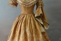 1850, pagoda/bell sleeves / The domed skirts of the 1840s continued to expand. Skirts were made fuller by means of flounces (deep ruffles), usually in tiers of three.  Wider bell-shaped or pagoda sleeves were worn over false undersleeves or engageantes of cotton or linen, trimmed in lace, broderie anglaise, or other fancy-work. Separate small collars of lace, tatting, or crochet-work were worn with morning dresses, sometimes with a ribbon bow.