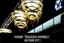 """Minimi """"Dialoghi Immobili"""" - AbitaMi 2011 / Slamp participates in the cultural display of MINIMI – Still Dialogues, edited by Laura Fiaschi and Gabriele Pardi from GumDesignI, majestic Chandeliers by Bruno Rainaldi have objects on the stage, creating a poetic and engaging scenery."""