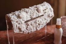 Luciana Bridal / SARAFREIKA BRIDAL COLLECTION, Accesorios Premium. Clutch de acrílico y solapa de piel con bordado de encaje, piedras y chaquiras. El proceso de elaboración es extenso y sólo sobre pedido. Dimensiones 16cm alto, 22cm largo, 4cm ancho. ....................SARAFREIKA BRIDAL COLLECTION, Premium Accesories. Rigid clutch in acrylic and leather flap with lace embroidery, beads and gemstones. The elaboration process is long and unique, on request only. Measurements 16cm height, 22cm lenght, 4cm depth.