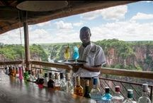 The Lookout Café / The Lookout Café is perched 120m above the turbulent rapids of the Zambezi River, overhanging a giant chasm of the Batoka Gorge, just downriver of the iconic Victoria Falls Bridge, which forms part of its spectacular backdrop. The semi open-air café offers one of the best view in Victoria Falls. The café offers a range of refreshing beverages, coffee and tea, as well as a lively cocktail menu.