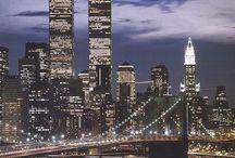 New York / Nova York, a mais rica e influente cidade do planeta pulsa dinamismo e agito cultural. Você já viu essas ruas, praças e edifícios em dezenas de filmes, mas uma visita in loco é sempre um encontro com o inusitado e o fascinante. É impressionante perceber que a verticalidade de seus arranha-céus, como o Empire State Building, combina perfeitamente com as linhas horizontais da Brooklyn Bridge ou os gramados do Central Park. Os musicais nas casas ao longo da Broadway complementam a grandiosidade de super-museus como o MoMA, o Metropolitan e o New Museum ou os disputados eventos esportivos em templos sagrados como o Yankee Stadium e o Madison Square Garden.   Seus restaurantes estão entre os melhores do mundo, não importa a especialidade, assim como seus hotéis. Aliás, hospedagem aqui é um dos custos mais altos para os viajantes. Para circular pela Big Apple abuse das linhas do metrô, sempre práticas e perto das melhores atrações, e evite os táxis para não correr o risco de ficar preso no famoso trânsito local. As opções de compras são as mais variadas que se pode imaginar, de brinquedos a roupas, de eletrônicos a livros raros, afinal não há cidade que melhor simbolize o capitalismo que Nova York, afinal, ícones como Wall Street e a Nasdaq estão aqui.  Para quem se sente meio claustrofóbico no meio de tanto concreto, a pedida são passeios pelo rio Hudson, Ellis Island ou a Estátua da Liberdade, a tríade que recebeu, por séculos, levas e levas de imigrantes que formaram a cara e a alma da cidade. Aqui é fácil ver um italiano bebendo uma cerveja irlandesa em Chinatown, ou um taxista paquistanês que consegue falar palavras em espanhol com seu colega dominicano. Ou seja, praticamente nada restou de suas raízes holandesas, quando a cidade era conhecida como Nova Amsterdã (o bairro do Harlem manteve o nome, mas a alma é puro jazz). Da velha York britânica a maior influência são belos edifícios coloniais perdidos nas sombras dos prédios vizinhos.  Curiosidade: Nova Y