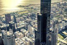"""Chicago / Para se apaixonar por Chicago é necessário apenas um minuto de frente para a Cloud Gate. No reflexo da escultura, em meio ao Millennium Park, todas as facetas da Cidade dos Ventos se revelam. Em movimentos contorcidos, os prédios dançam a cada passo em direção à escultura do artista Anish Kapoor. Ali, debaixo daquele grande feijão prateado (como os próprios moradores apelidaram), não há quem resista à beleza de Chicago. O passo é apenas o primeiro para quem chega à metrópole banhada pelo grandioso Lago Michigan. Fazemos, no entanto, um alerta: o passeio é tão incrível que talvez você o repita muitas vezes ao longo da viagem ou mesmo ao longo da vida!    Em Chicago – ou Chi-Town, como chamam os locais – a vida corre em ritmo desacelerado. Apesar de ser a terceira cidade mais populosa dos Estados Unidos – com 2,7 milhões de habitantes – a Wind City consegue manter o equilíbrio entre a correria de um grande centro urbano e a calmaria de um ambiente repleto de parques à beira de um magnífico – e grande – lago. Localizada no estado de Illinois, no centro-oeste dos Estados Unidos, Chicago surpreende e conquista rapidamente os visitantes que chegam por lá.    A cidade tem o dom de transformar, em pouco tempo, o viajante em um local. É desses lugares que dá gosto de participar da vida diária e não apenas cumprir metas turísticas. Aliás, em Chicago os pontos turísticos são frequentados por todos. É fácil encantar-se com a engenhosidade do """"L"""", onde moradores percorrem os trilhos do metrô de superfície dando voltas pelo Loop, enquanto na janela do vagão a paisagem é composta por dezenas de prédios inovadores. Ao mesmo tempo, pertinho do disputado The Bean, cadeiras de praia servem de poltrona ao ar livre para quem quer assistir a um clássico do cinema na grande tela do Jay Pritzker Pavilion. Por todos os lados os turistas seguem, em total harmonia, em meio aos locais.  Quem vê hoje Chicago tão organizada, segura (lembrando que ela já foi dominada por gângsters, como"""
