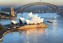 """Sydney / Sydney  G'day mate! É assim o """"bom dia"""" na Austrália, ou """"Oz"""", como eles mesmos gostam de dizer. Capital do estado de New South Wales (Nova Gales do Sul), Sydney costuma ser confundida com a capital da Austrália, que na verdade é Camberra. A metrópole com cerca de 4,8 milhões de habitantes é a maior do país e concentra cerca de 20% da população nacional, e mesmo não sendo a capital, em alguns aspectos é quase como se fosse.   A cidade mais visitada da Austrália é vibrante, moderna e segura. Fundada em 1788, sua história recente começa quando os pioneiros britânicos decidem fundar uma colônia penal no local. E no desenrolar dos fatos, de colônia penal e terras aborígenes, povo que ocupa o país há milhares de anos, ela se transformou na maior cidade da Oceania. Ela é como uma síntese do que a Austrália reserva aos seus visitantes.    Sydney-opera-house  Não é em vão que muitas pessoas visitam Sydney e já pensam em se mudar para lá. A Austrália está sempre no topo da lista entre os países com melhor qualidade de vida do mundo e, por ser um local aberto a imigrantes, você encontra pessoas-e comida-de todo lugar. Australianos, ingleses, chineses, japoneses, mexicanos, brasileiros… É uma cidade onde as pessoas são atraídas pelas oportunidades e envolvidas pelo clima de tolerância às diferenças.     Sydney é uma cidade urbanizada, com escritórios de multinacionais, edifícios altos, movimento constante de pessoas e veículos… Até o trânsito de embarcações na Baía de Sydney é de causar surpresa. Ao mesmo tempo, é um lugar que resgata hábitos simples. Ser cumprimentado por um anônimo com um sorriso ou curtir uma tarde na praia depois do trabalho é comum. O estilo de vida australiano que muitos almejam é superintessante; o país tem um povo acolhedor, amigável e, muitas vezes, desprendido.    Sydney-opera-house Sydney-harbour-bridge Sydney-tower-eye Luna-park Coastal-walk-bondi-coogee  Seu símbolo maior, a Opera House, é certamente um passeio imperdível. Para quem não q"""