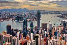 """Hong Kong / Hong Kong  Movimentada, cosmopolita, exótica e plural. Hong Kong é uma ilha no sudeste da China, que tem uma densidade demográfica altíssima e o maior número de arranha-céus do mundo! É um lugar que mistura um pouco da tradição chinesa à modernidade europeia, fruto da colonização inglesa que por 156 anos esteve presente na ilha. Após esse período, Hong Kong se tornou uma região administrativa especial da China e permanece ainda hoje como um grande centro financeiro e portuário da Ásia.   Hong Kong é o que poderíamos chamar de cidade-estado. Embora não seja completamente independente da China e viva sobre o princípio de """"um país, dois sistemas"""", o lugar tem uma moeda própria, o dólar de Hong Kong, tem um governo próprio, leis próprias e duas línguas oficiais, o chinês o inglês. Brasileiros não precisam de visto para visitar o país — assim como precisam para ir à China continental — e em Hong Kong o capitalismo rola solto, não há limitação à internet ou qualquer coisa do tipo.    Victoria-peak  A cidade-estado tem pouco mais de 1.104 quilômetros quadrados e cerca de 40% de seu território é destinado aos parques e reservas naturais. Pela falta de espaço e com uma população com mais de 7 milhões de pessoas, Hong Kong aprendeu a crescer para cima, o que fez com que hoje a quantidade de edifícios seja imensa! Moradias, shoppings, restaurantes, lojas e escritórios estão sempre em edifícios que crescem para cima e, eventualmente, para baixo também. Com um espaço pequeno e tantas pessoas, outro campo que precisou se desenvolver foram os transportes e hoje o sistema de transporte público de Hong Kong é muito eficiente. A cidade tem ônibus de dois andares e um sistema de metrô de excelente qualidade, muito fácil de usar.   Andando pelas ruas de Hong Kong, fica evidente a herança da China, afinal, mais de 90% da população é de origem chinesa, mas também fica claro que Hong Kong é uma cidade global, moderna, que tem grandes redes hoteleiras, restaurantes de redes int"""
