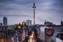 """Berlin / Berlim  É impossível andar pelas ruas de Berlim e não sentir a energia que se faz presente em cada esquina da bela capital da Alemanha. Uma metrópole pulsante e rica em história, onde o antigo e o novo se misturam com perfeição; um verdadeiro celeiro de arte e cultura - com opções de entretenimento para todos os tipos de público -, gastronomia de qualidade, entre tantos outros motivos que fazem desse um dos destinos europeus mais procurados por turistas do mundo todo.  Caminhar sem pressa pelas ruas da cidade, além de ser algo bastante agradável, faz com que o visitante experimente um mix de sensações, sendo a admiração - com certeza - uma constante diante da grandiosidade e da beleza de monumentos como o Portão de Brandemburgo (1789-91), além de outros pontos de interesse como o Reichstag (sede do parlamento alemão), a Catedral de Berlim (Dom) e a Torre de TV.  Também é impossível não se emocionar e não """"parar"""" para refletir ao encontrar nessas mesmas ruas os sinais de um passado sombrio e não muito distante, marcado pelo comando de Adolf Hitler - pelos horrores e pelas consequências da guerra - além, é claro, da fase posterior, quando a cidade ficou dividida pelo muro. Símbolo da Guerra Fria, a estrutura foi derrubada em 9 de novembro de 1989, uma data muito importante que mudou a mentalidade do mundo.  Biergartens  Apesar do ritmo frenético em suas ruas e avenidas, Berlim é uma metrópole onde fica fácil se locomover, pois, além de áreas próprias para o trânsito de pedestres, a cidade conta com um sistema de transporte público extremamente eficiente. Os parques e os famosos biergartens - jardins onde é possível degustar a cerveja alemã e várias delícias da culinária - são áreas excelentes para quem deseja fugir um pouco do movimento. Em dias de sol, esses lugares são imbatíveis!    Assim como em toda a Alemanha, a moeda local é o Euro (confira a cotação aqui) e o idioma oficial é o alemão, apesar de o inglês ser uma língua bastante comum nos principais po"""