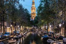 """Amsterdam / Amsterdã  Um simples passeio a pé pelas ruas de Amsterdã - ou uma pedalada, caso queira se juntar aos moradores locais - e já é possível entender perfeitamente por que a capital dos Países Baixos é um dos destinos mais procurados por turistas do mundo inteiro.  Rodeada por canais, pontes e ciclovias, repleta de construções antigas (com janelas enormes que mais parecem vitrines) e paisagens de tirar o fôlego, a cidade também possui uma vida cultural intensa. Mas a verdade é que, apesar dessa movimentação toda, Amsterdã não decepciona aqueles que desejam uma estadia tranquila ou até mesmo romântica.  A cidade vibrante oferece uma série de opções de cultura e entretenimento, a exemplo de alguns museus internacionalmente famosos, como o Van Gogh e o Rijsk, e parques muito bem estruturados, como o Vondelpark.  Os tradicionais bares que servem a famosa cerveja holandesa também estão por todos os cantos, além de boates, casas de shows e restaurantes com culinária para todos os gostos. Como não poderia deixar de ser, o povo holandês é extremamente amigável, comunicativo e adora uma celebração.   Holanda ou Países Baixo?  Afinal, qual seria o termo correto? Muita gente não sabe, mas Países Baixos é a denominação oficial. A explicação para o segundo nome é que realmente existiu uma província chamada Holanda inserida na região onde hoje se encontram os Países Baixos.  Essa província surgiu como uma potência dominante no século XVII e por isso o nome é tão famoso no mundo todo, inclusive no Brasil. Atualmente, a região da antiga Holanda corresponde às províncias da Holanda do Sul e da Holanda do Norte (onde está Amsterdã).  Vanguarda  O idioma oficial dos Países Baixos é o holandês e os nativos ficam felizes quando o visitante se esforça para pronunciar algumas frases como """"Dank u wel"""" (""""Dank ú vel"""" como se diz em português), o mesmo que """"muito obrigado"""".  Porém, cada vez mais habitada por estrangeiros - atualmente são mais de 700 mil -, a língua inglesa está bastan"""