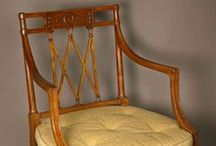 Sheraton 1795-1815 (Georgian Era-King George III) / Named for Thomas Sheraton, designer.  Last great furniture style of 18th century England. Most recognizable difference from Hepplewhite are the chair backs.  Sheraton preferred square backs and Hepplewhite oval backs. Typical trait of Sheraton is fluting or reeding of legs on tables or sideboards.  Used Satinwood, Mahogany, Tulipwood, rosewood and ebony.  Neo-Classical; coincides with French Directoire style.