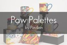 Paw Palettes by Pavilion / Gretchen Kish Serrano founded Paw Palettes to share her collection with art and pet lovers. Each piece features bold and colorful paintings of our favorite pets. Find your favorite breed including Black and Yellow Labs, Golden Retrievers, Bulldog, West Highland Terrier, Pug, Dachshund, Tuxedo Cat, Tabby Cat, and more. Featuring coaster box sets, journal and pen sets, magnet sets, key chains, boxed mugs, and wood framed canvases.