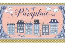 "Parapluie / Parapluie is a fabric collection celebrating the city of light and love. French for umbrella, Parapluie takes us on a walk through Paris in the rain. From ""bicyclettes"", to cobblestone streets, famous landmarks, palatial buildings, quaint neighborhoods and even a little escargot, this city is one to be enjoyed ""en plein air."""