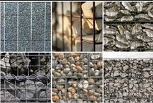 """Gabion / A gabion (from Italian gabbione meaning """"big cage""""; from Italian gabbia and Latin cavea meaning """"cage"""") is a cage, cylinder, or box filled with rocks, concrete, or sometimes sand and soil for use in civil engineering, road building, and military applications. For erosion control, caged riprap is used. For dams or in foundation construction, cylindrical metal structures are used. In a military context, earth- or sand-filled gabions are used to protect artillery crews from enemy fire."""