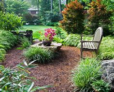 """A secluded """"meditation circle"""" provides a quiet spot in front of this house, not far from the street but sheltered by an American beech hedge. Japanese forest grass thrives in the shady environment."""