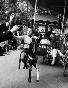 Alfred Eisenstaedt, Little boy on merry-go-round at the Tuileries Gardens, sticking out his tongue, 1963.