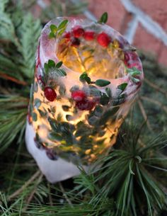 cute idea ... don't k mow how long it will last ... berries and boxwood in ice to make candle holder - use outside on patio or by fire pit