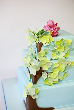 Tree cake with a pink bird on top.