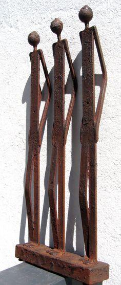 Esta escultura esquemática representa a tres cuerpos humanos que en esta imagen se están apoyando en una pared. La posición de sus brazos ayudan a dar la sensación de que realmente se están apoyando. El material utilizado es el metal, pero parece que esta un poco oxidado.