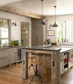 The reclaimed wood accents in this kitchen give it laid back vibe, while the dark granite countertops, and the metal accents keep it from being too rustic. I'm in love with the large windows, looking out onto greenery, and the glass paned door.