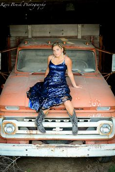 2014 High School Senior girl for posing picture ideas. Old barn, old truck, prom dress...vintage look. Modeling on an old Chevy truck in her prom dress and cowboy boots. Trash the dress photo shoot session.