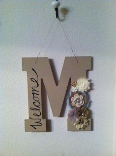 "DIY home decor... with bright flowers and ""Mikaela"" instead of ""Welcome"""