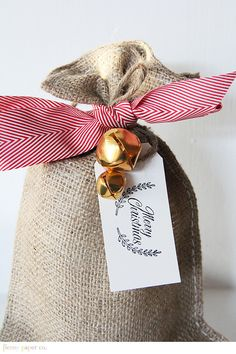 burlap bags tied with red herringbone ribbon... stylish Christmas gift wrap