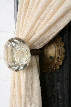 Vintage door knobs as curtain holders.