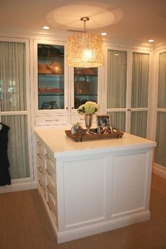 a fabulous walk-in closet with shirred drapes behind glass doors