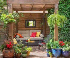 A wood pergola shelters a daybed at one end of the brick patio that homeowner Holly Fliniau built off the breezeway to the garage. The bed backs up to a board fence that she shares with her neighbor. Colorful potted plants mark the outdoor room's entrance and soften the structure's beefy support posts.