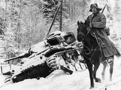 A horseback rider of the Red Army cavalry, clad in heavy winter gear, is seen as he passes a German tank abandoned by the retreating German invaders, at an unknown location along the German-Russian front, on February 22, 1942.