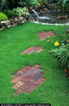 Bricks laid out in a playful asymmetrical pattern create a pathway to a pond beyond.