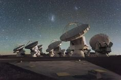 """Antennas of the Atacama Large Millimeter/submillimeter Array (ALMA), on the Chajnantor Plateau in the Chilean Andes. The Large and Small Magellanic Clouds, two companion galaxies to our own Milky Way galaxy, can be seen as bright smudges in the night sky, in the centre of the photograph.  (Credit: ESO/C. Malin) Mona Evans, """"Hidden Universe 3D - film"""" http://www.bellaonline.com/articles/art183545.asp"""