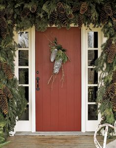 Christmas Pine Cone door swag with flocked sugar pine cones and lichen-covered twigs accented with incense cedar and other holiday greens on Country Living
