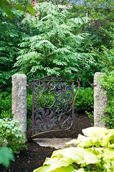 A gate crafted from salvaged gears swings between granite posts marking a dog run.
