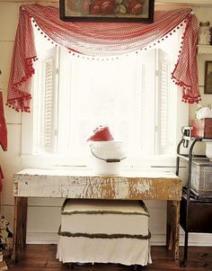 Shabby Rustic kitchen uses a swag of red-and-white gingham over white hinged Colonial shutters.