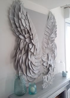 Gorgeous stretched canvas angel wings displayed over this mantel!