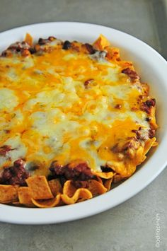 Frito Chili Pie -- 2 cups Fritos corn chips 3 cups chili 8 ounces cheddar cheese 8 ounces Monterrey Jack cheese Sour cream (optional garnish) green onions (optional garnish) Instructions Preheat oven to 350 degrees. Layer Fritos in the bottom of a baking dish topped with chili. Bake for 15 minutes, or until cheese is melted. Remove from oven and serve warm with a dollop of sour cream and topped with chopped green onions!