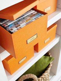 Store your collection in decorative storage. There are more affordable and design-friendly storage boxes available now than ever before. I love the idea of organizing your movies and games by genre in boxes like these orange ones showcased over at Better Homes and Gardens (they're either the same or similar to The Container Store Stockholm line).